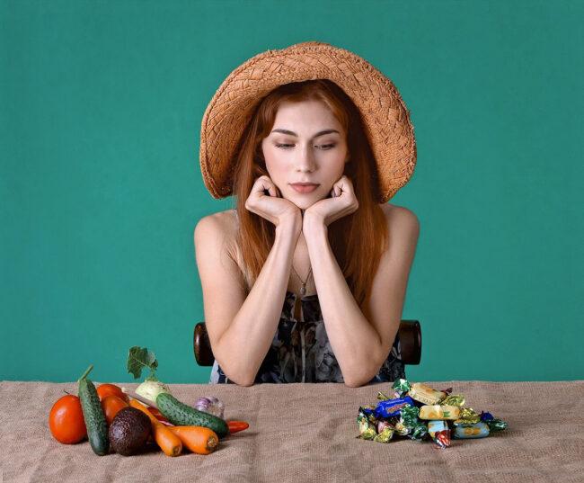 kobieta zastanawiająca sie nad rodzajem przekąski - słodycze czy warzywa